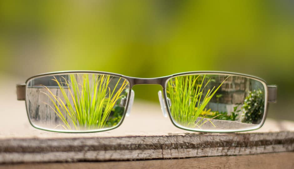 glasses with blades of grass in focus