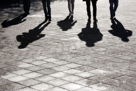 Legs and shadows of people walking.