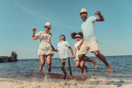 Happy,African,American,Family,Holding,Hands,And,Jumping,On,Beach