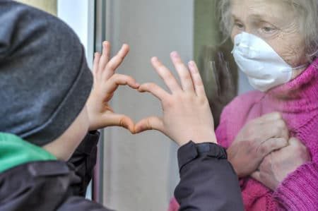 Grandmother,Mature,Woman,In,A,Respiratory,Mask,Communicates,With,Her
